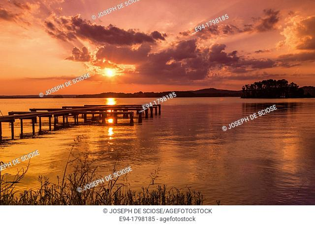 Sunset over a lake with a small boat dock silhouetted in the foreground, Lake Guntersville State Park, Alabama, USA