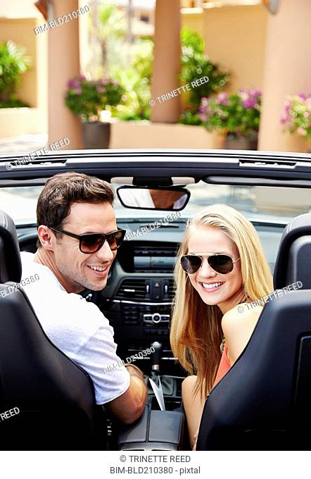 Couple sitting in convertible outdoors