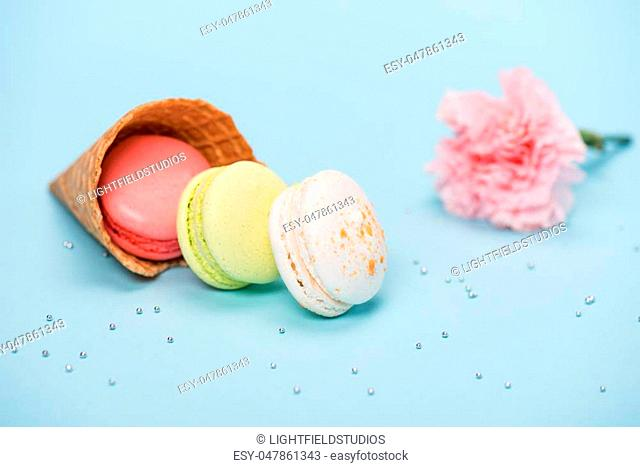 Group of handmade macarons in waffle cone and pink flower on blue surface. macarons background concept