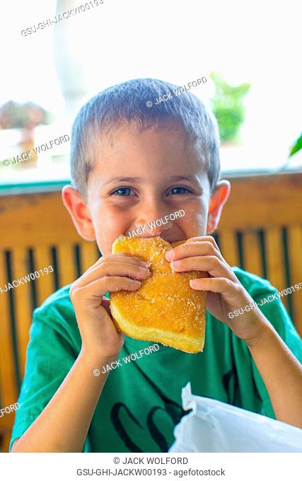 Young Boy Eating Malasada, Hawaii, USA
