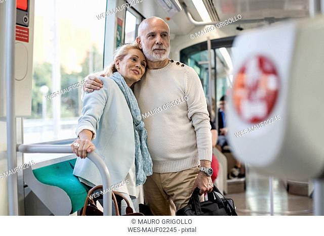Affectionate senior couple standing in a tram