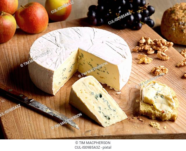 Still life of Blue brie with walnuts, grapes and apples on chopping board