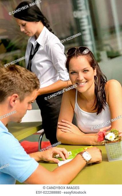 Couple at cafe man looking at menu