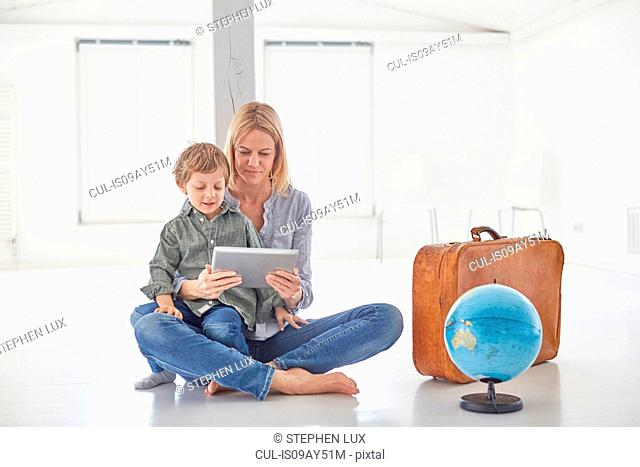 Mature woman and son sitting on floor looking at digital tablet