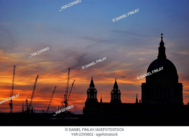 St. Paul's Cathedral in London, England, and cranes from the many building sites near it, seen against a spectacular sunset