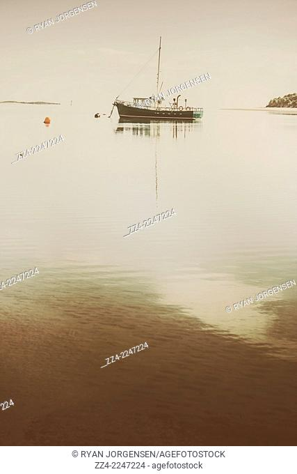 Old style image of a fishing boat trawler docked at Tasmanian harbor at dawn. Taken Port Sorell, Australia