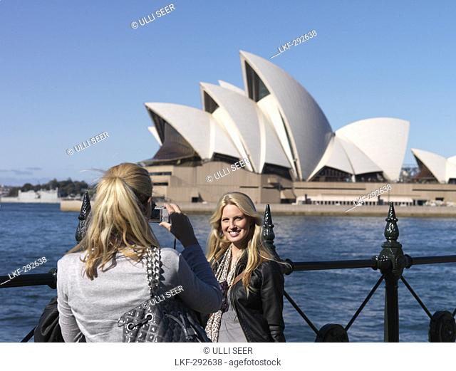 Two young women, Sydney Opera House in background, Sydney, New South Wales, Australia