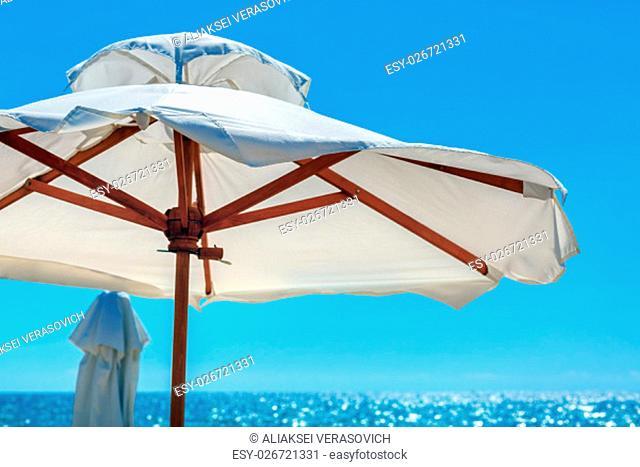 Big white parasol on a background of bright blue sky close-up. Beach umbrella
