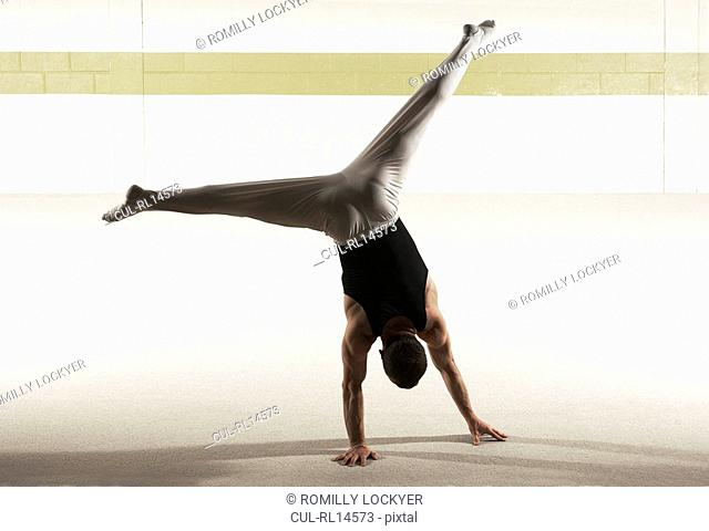 Male gymnast performing floor exercise, rear view