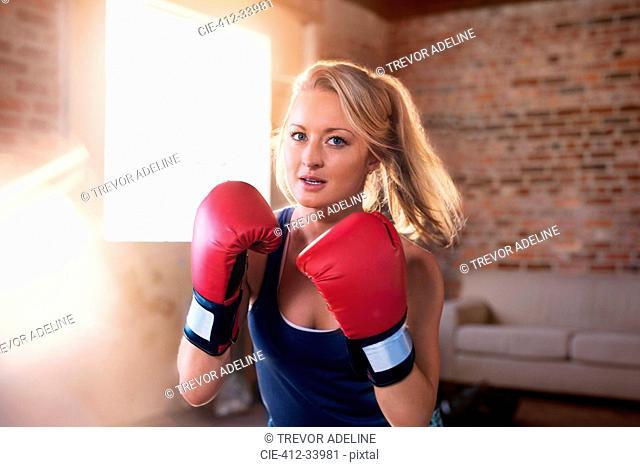 Portrait tough young woman boxing in studio