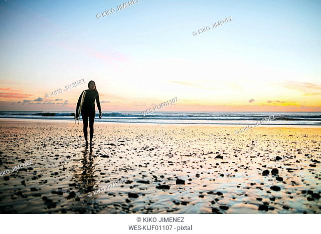 Young woman with surfboard walking on the beach by sunset