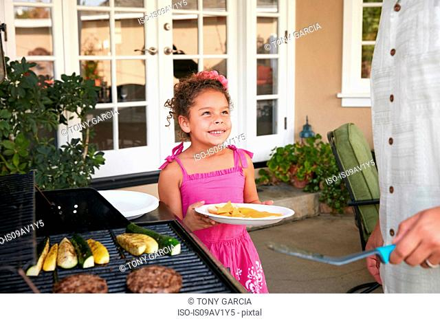Girl on patio holding plate being served barbeque food by father