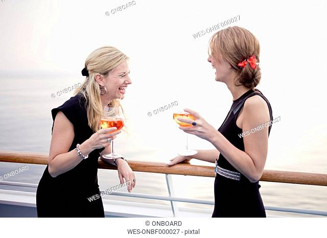 Two laughing women with aperitive stending on deck of a cruise liner
