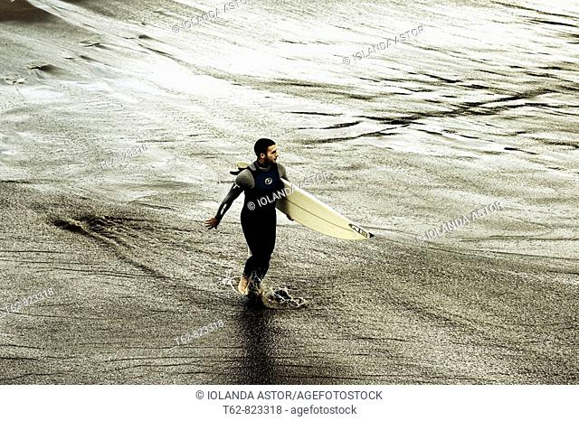 Surfing Young man entering the water
