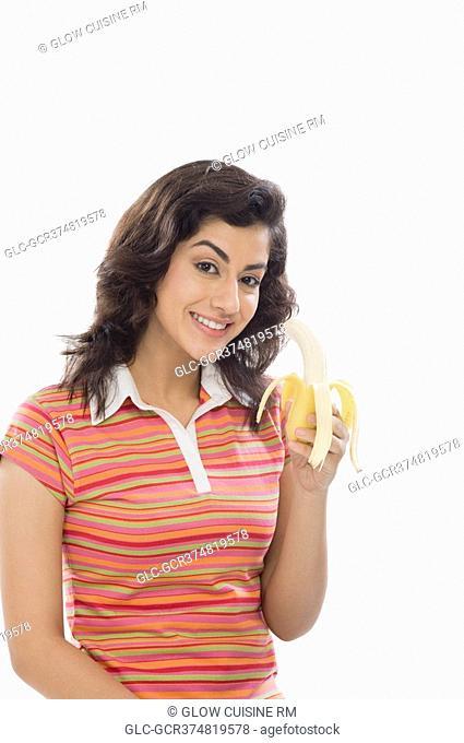 Portrait of a woman eating a banana