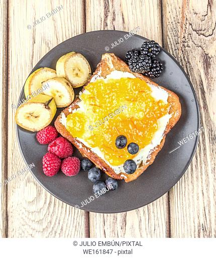 aerial shot of French toast with fried banana and berries spread on butter and jam, on natural wood