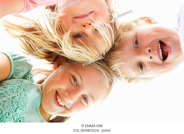 Low angle portrait of boy and two girls outdoors