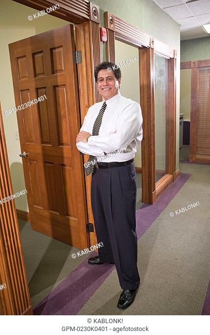 Portrait of mature businessman standing in office with arms crossed, smiling