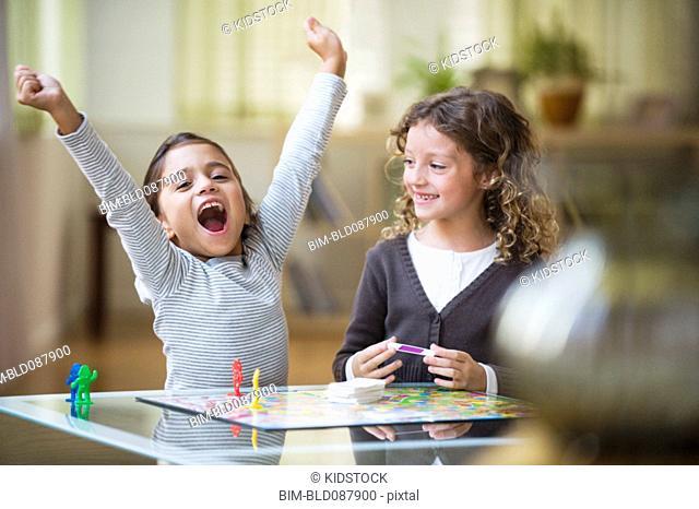Mixed race girls playing board game
