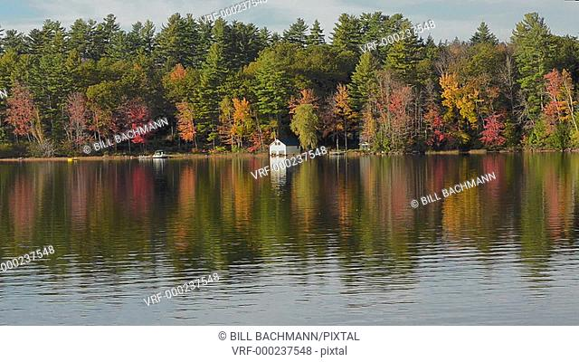 Norway Maine beautiful fall scene of Lake Pennasseewassee with summer homes and fall colors in leaf peeping October with reflections in the water in Northern...