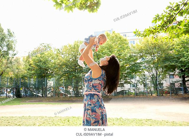 Grandmother holding up baby granddaughter in park