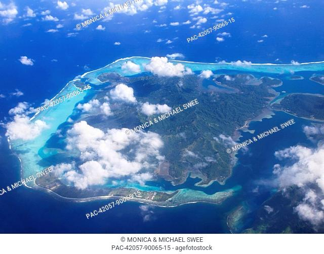 French Polynesia, aerial over atoll, view from above small white clouds outer barrier reef surrounds inner lagoon