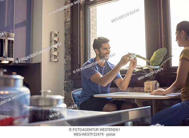 Young couple in kitchen taking smart phone pictures