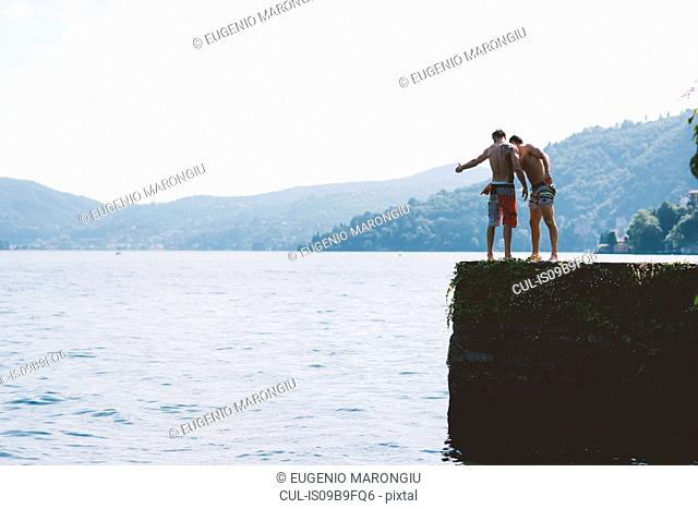 Two young men looking down from pier, Lake Como, Lombardy, Italy