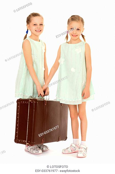 two pretty, slender little girls,sisters, in a very short summer dresses holding a large suitcase . Girls are preparing parents to go to a resort - Isolated on...