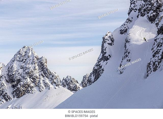 Caucasian climber scaling snowy mountain slope