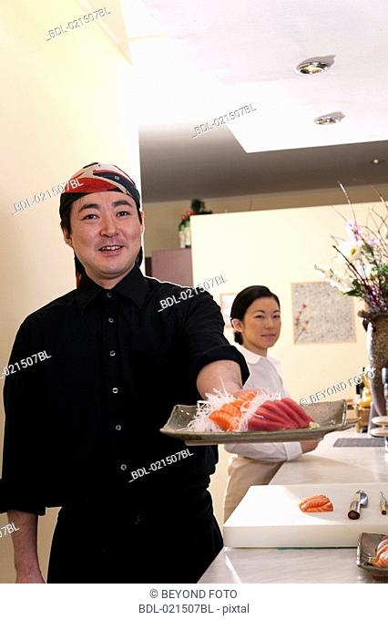 portrait of japanese chef presenting plate with sushi
