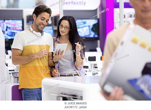 Couple looking at digital tablet in electronics store