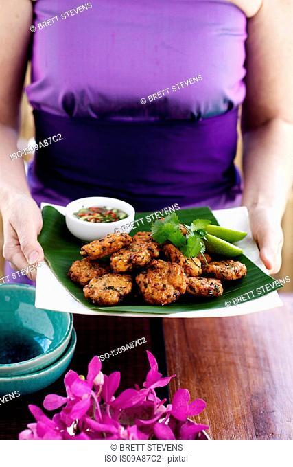 Woman carrying fishcake appetisers with coriander, lime and hot sour dipping sauce