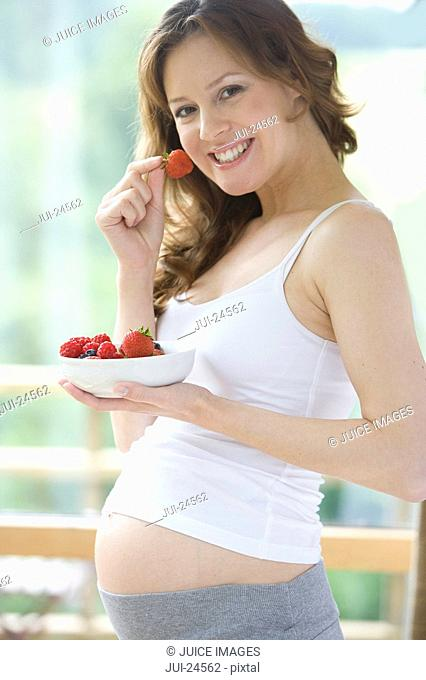 Smiling pregnant woman holding bowl of strawberries and eating one