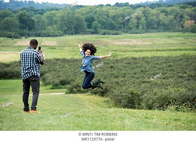 A man taking a photograph of a woman leaping in the air, jumping for joy with her arms outstretched