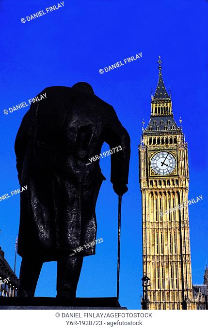Statue of Winston Churchill, portrayed as a very old but bullish man, looking at Big Ben in Westminster, London, England, on a Winter day of intense sunshine