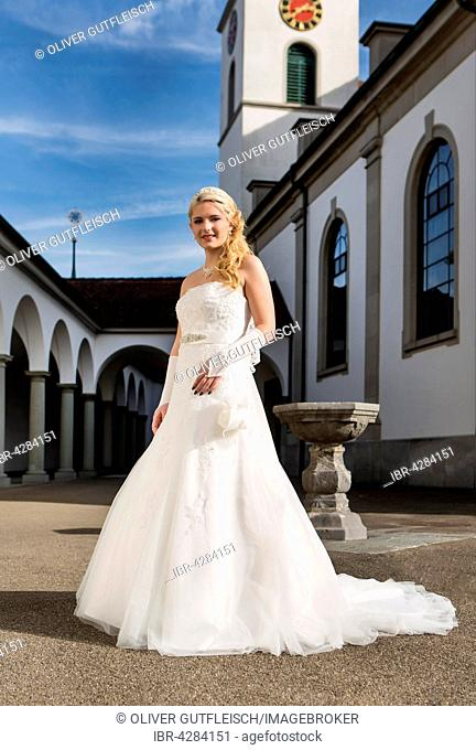 Young woman in white long wedding dress in front of church