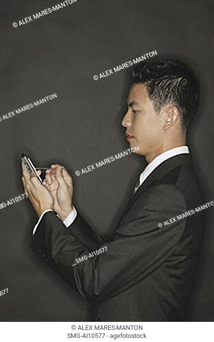 Young man using PDA, standing in profile
