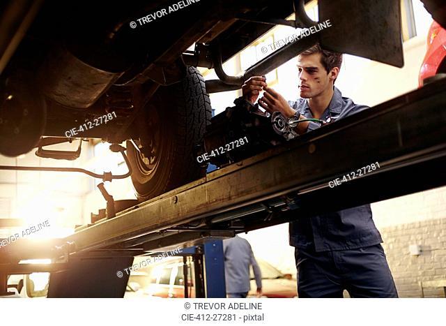Mechanic working under car in auto repair shop