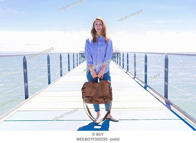 Italy, Lignano Sabbiadoro, portrait of young woman standing on sea bridge