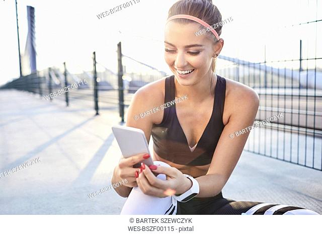 Happy woman with smartphone after urban workout