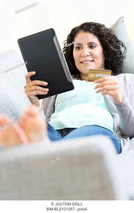 Hispanic woman using digital tablet on sofa