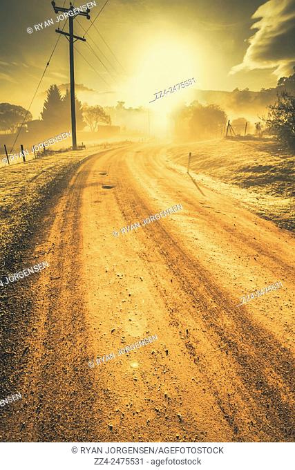 Rural Australia dirt road winding into a foggy sunrise, morning scene captured Judbury, Tasmania, Australia