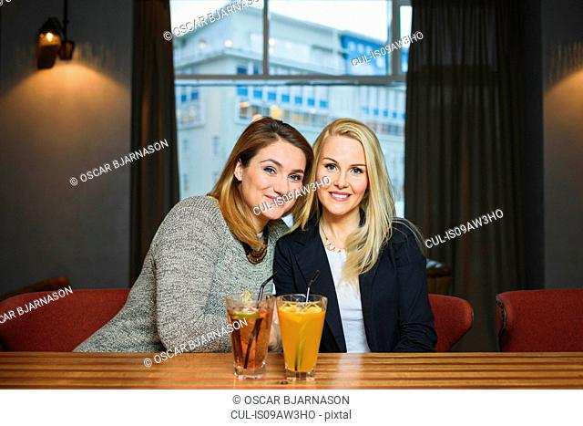 Mid adult women sitting at counter in public bar with cocktails looking at camera smiling