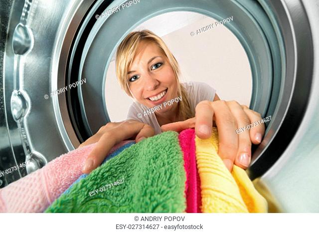 Close-up Of Young Smiling Woman Inserting Clothes In Washing Machine