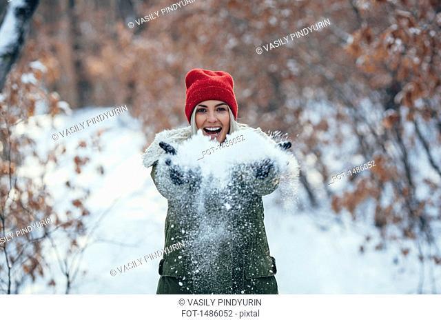 Portrait of happy young woman playing with snow