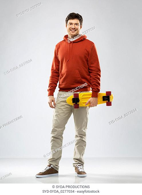 smiling young man in hoodie with short skateboard