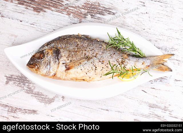Grilled fish on plate, top view