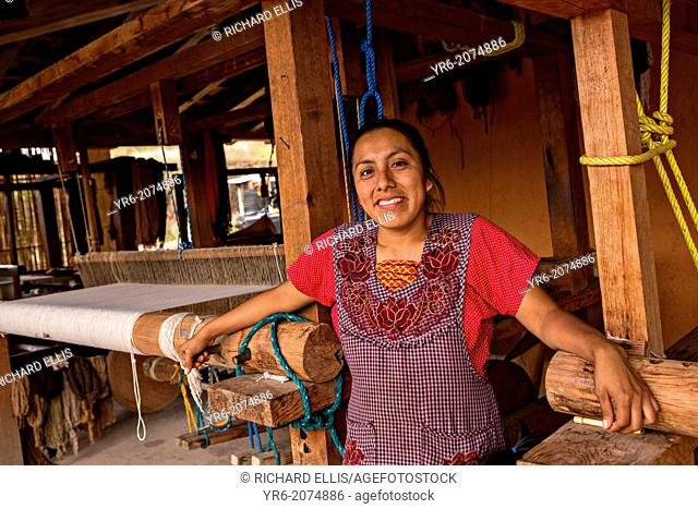 A Zapotec indigenous woman poses in front of her hand loom used to weave traditional carpets October 30, 2013 in Teotitlan de Valle, Mexico
