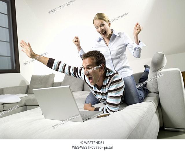 Couple on sofa, using laptop